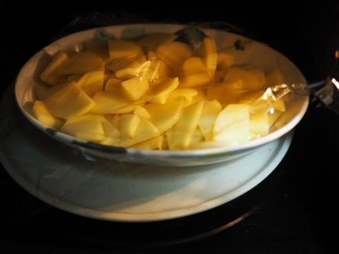 薄切りにしたじゃがいもを耐熱皿に並べてラップをかけて、レンジでチンする。